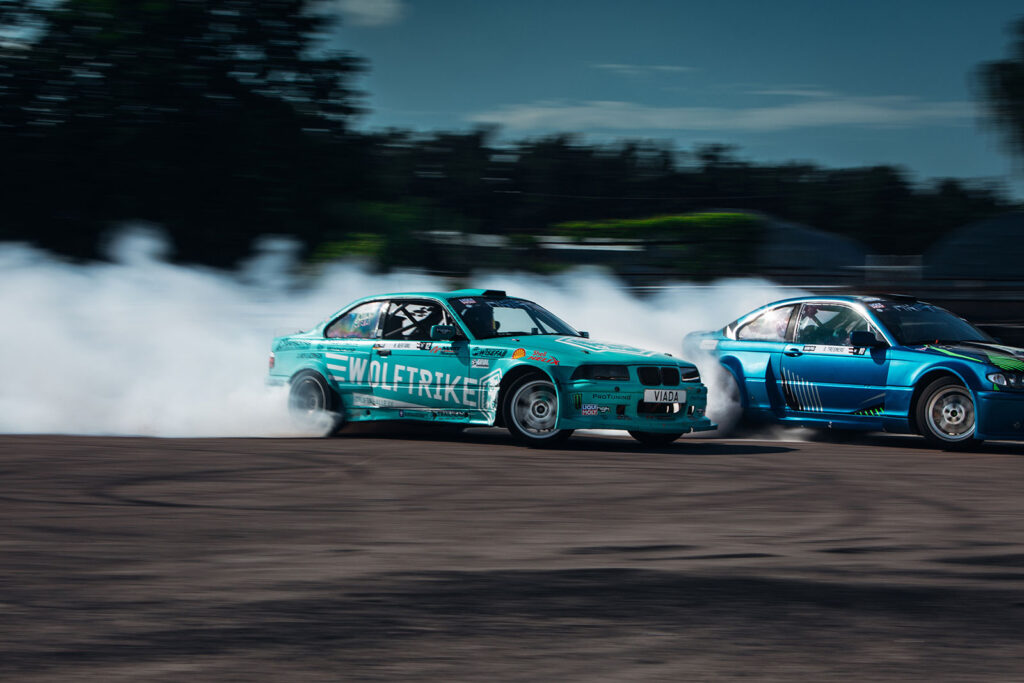 Two races cars with smoke behind them