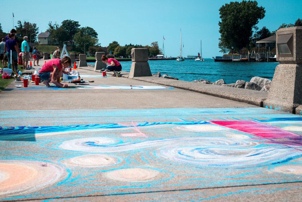Children doing sidewalk art with chalk by the ocean