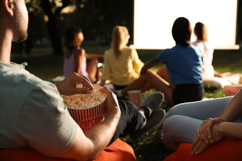Young adults sitting on the ground eating popcorn watching a projector screen