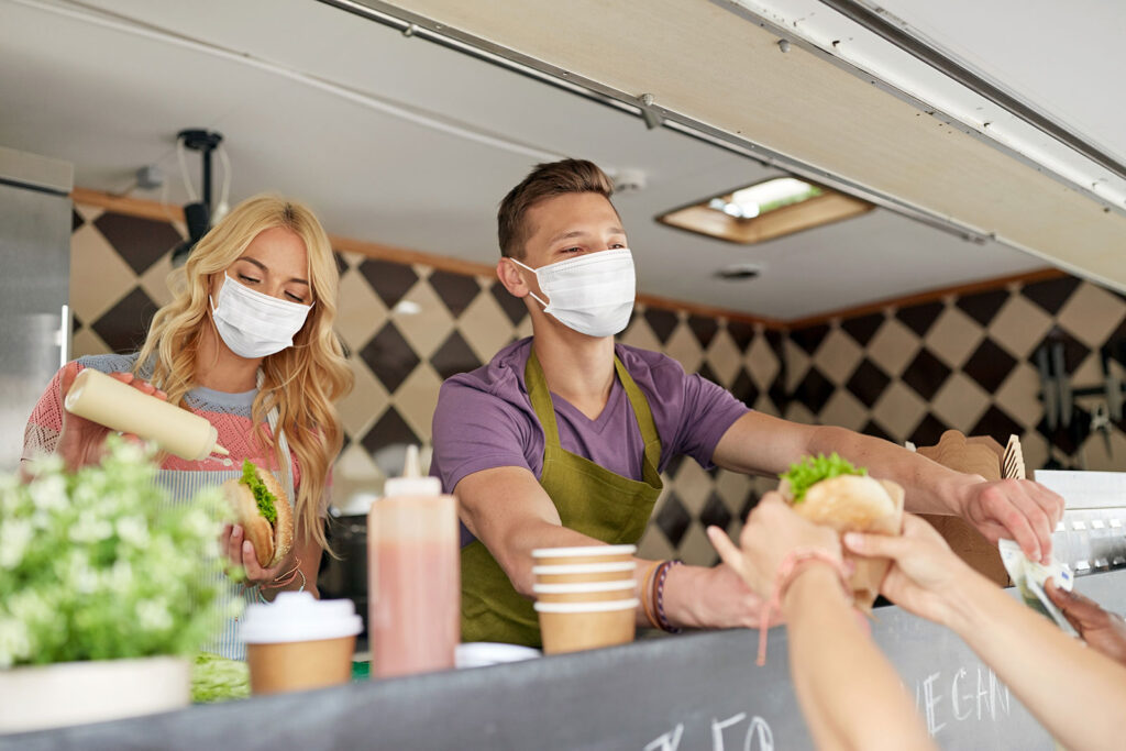 Adult male and female wearing mask serving food out of a food truck