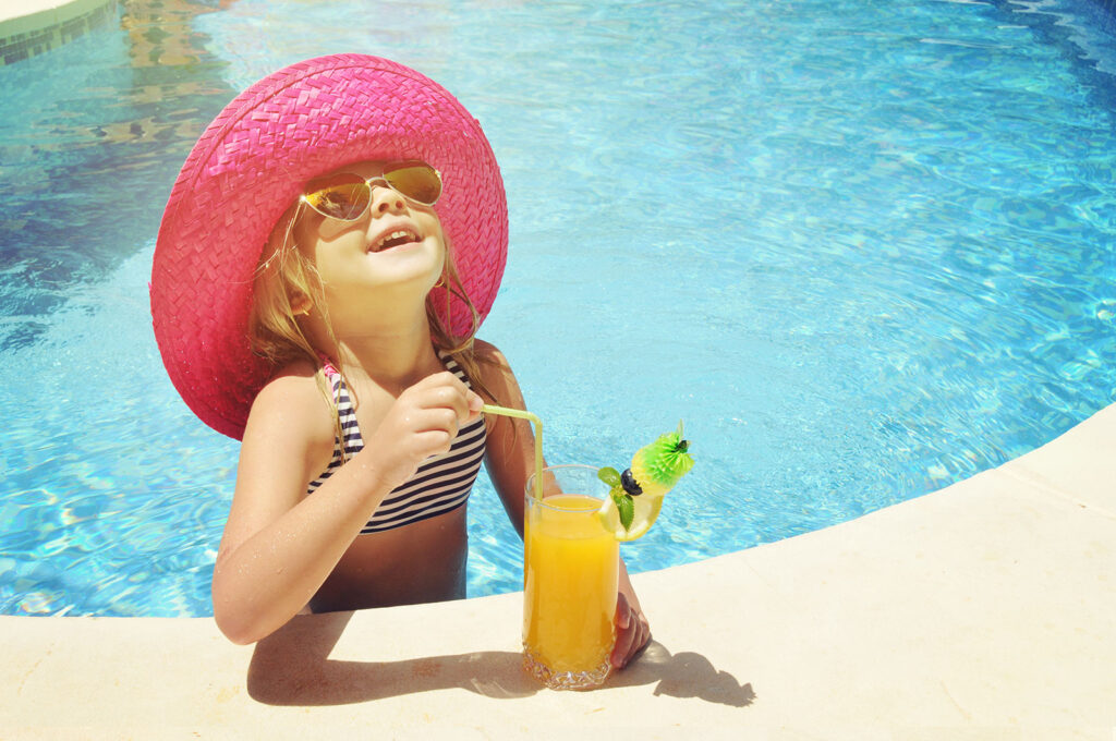 Little girl enjoying a refreshment in the pool