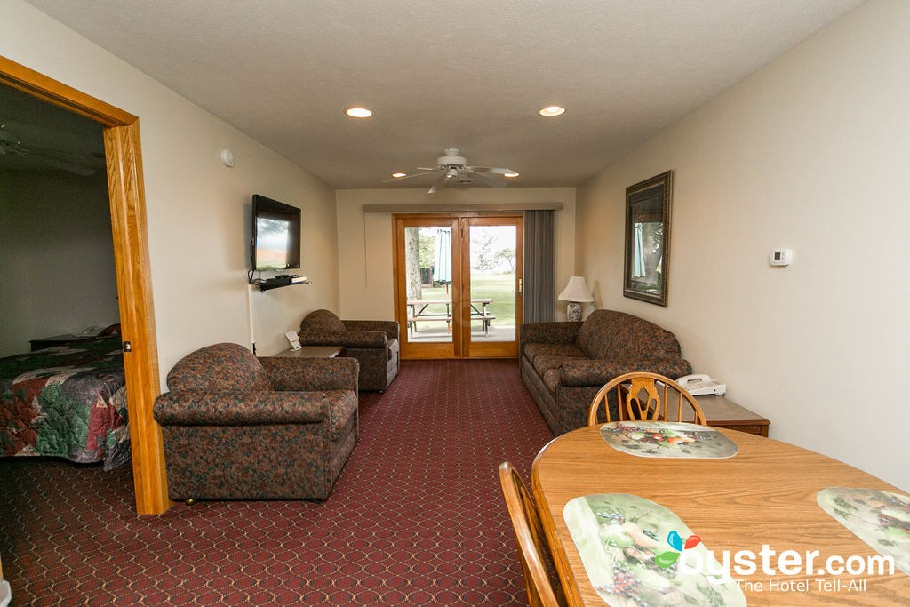 Hotel view of living room with furniture and kitchen table