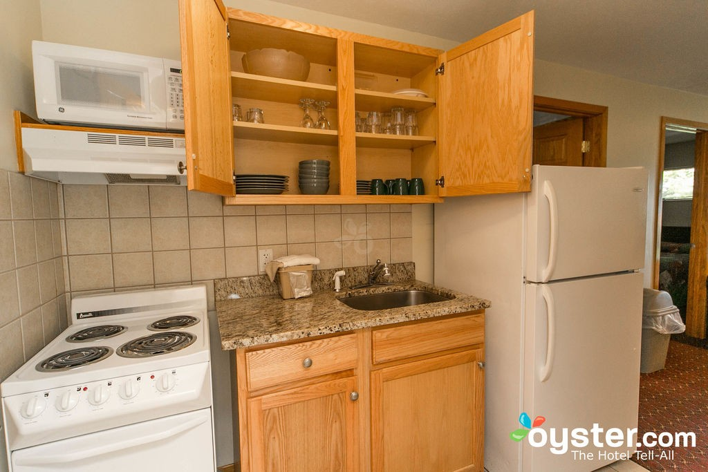 Hotel kitchen with cabinets with dishes and stove and fridge