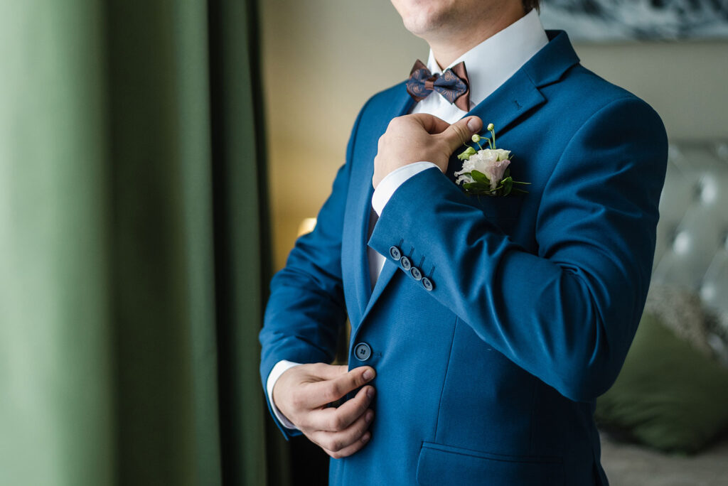 Man in tux adjusting his suit