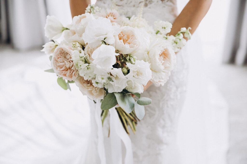 Wedding, woman holding her bouquet in her wedding dress